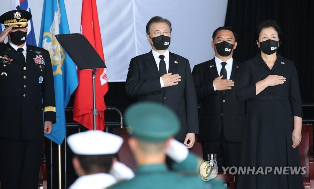 当地时间9月22日,在美国希卡姆空军基地第19机库举行的韩美两军烈士遗骸交接仪式上,文在寅夫妇向国旗敬礼。 韩联社