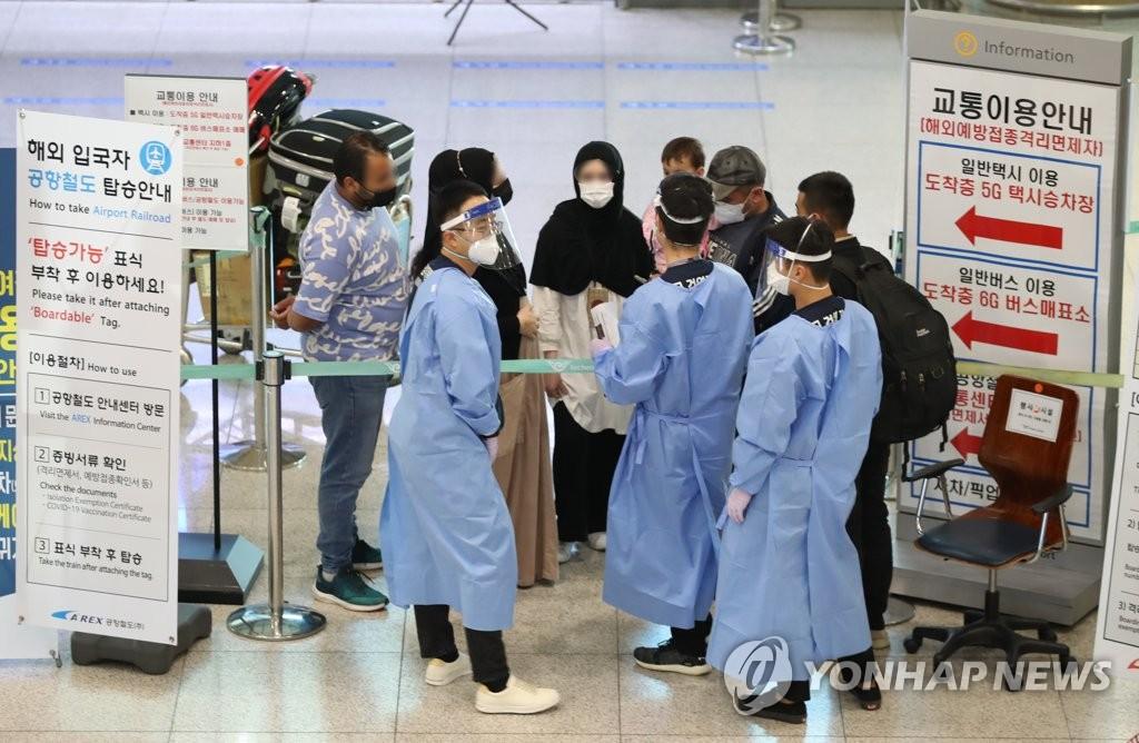 资料图片:入境人员接受机场防疫人员引导。 韩联社