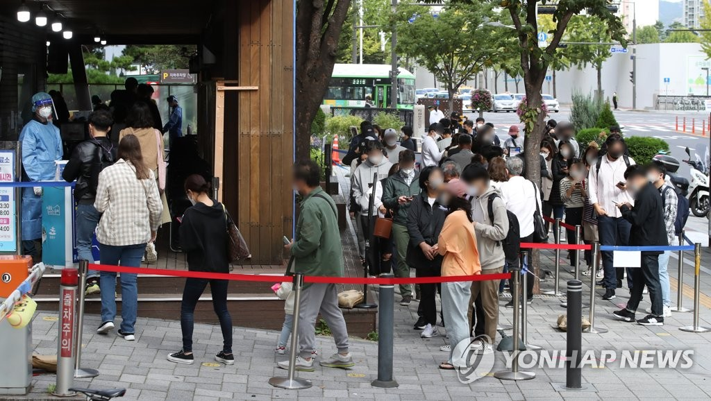 10月12日,在首尔松坡区卫生站筛查诊所,市民们排队候检。 韩联社