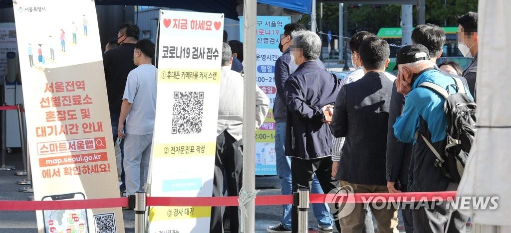 10月13日,在首尔站临时筛查诊所,市民们排队候检。 韩联社